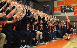Senior Tim Coen leads the student section in roller coaster during a home basketball game. The student section, known as