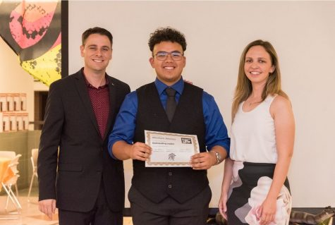 Senior Abraham Jiminez receives the Outstanding Leader Award for the 2019-2020 season from Mr. DuPlessis (left) and Ms. Holste (right) at the band banquet. Last year marked the end of the typical marching band season for many seniors like Jiminez